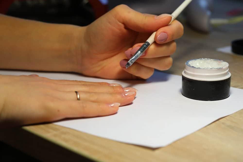 woman applying nail strenghener