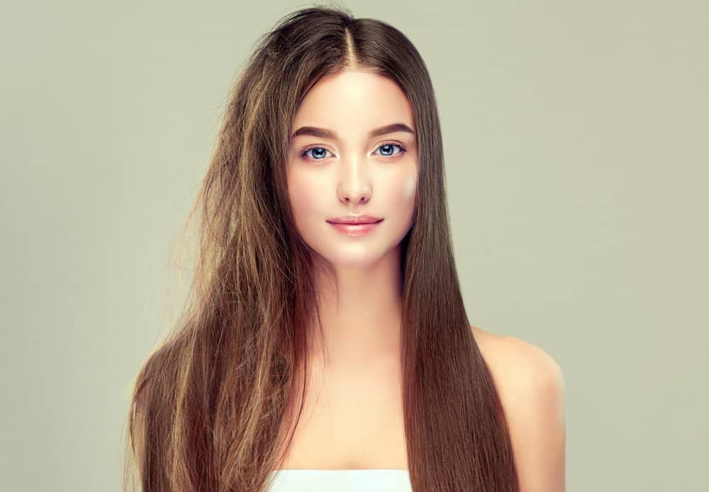 A long-haired woman with half her hair frizzy, half perfectly smooth