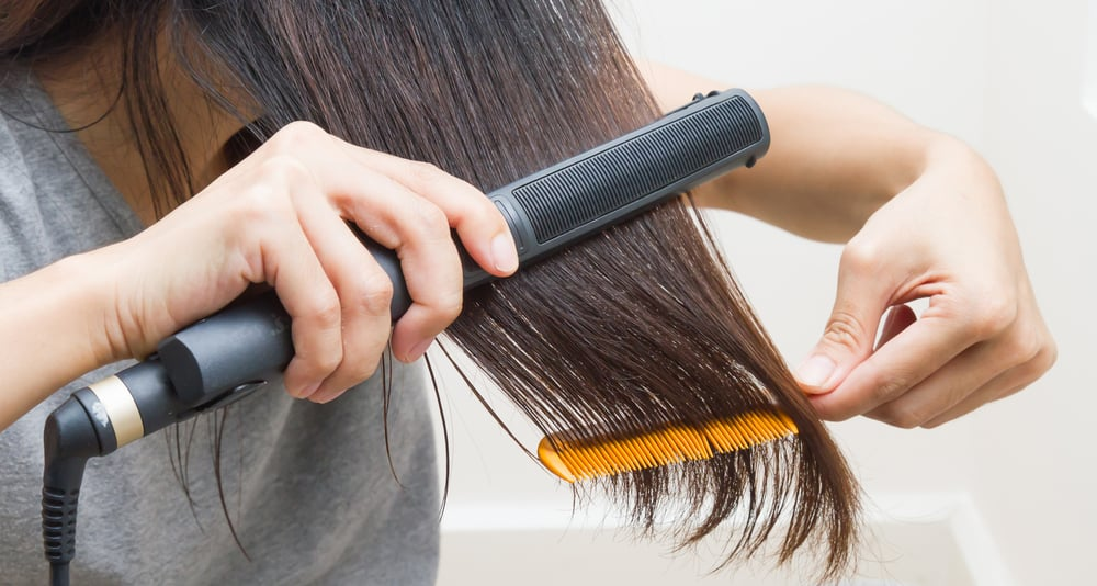 A woman is straightening her hair using a flat iron