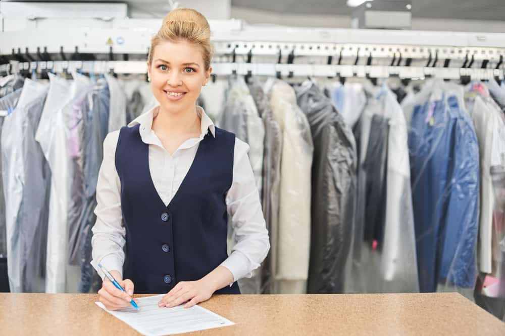Woman at a counter filling out a paper with dry cleaning rack behind her