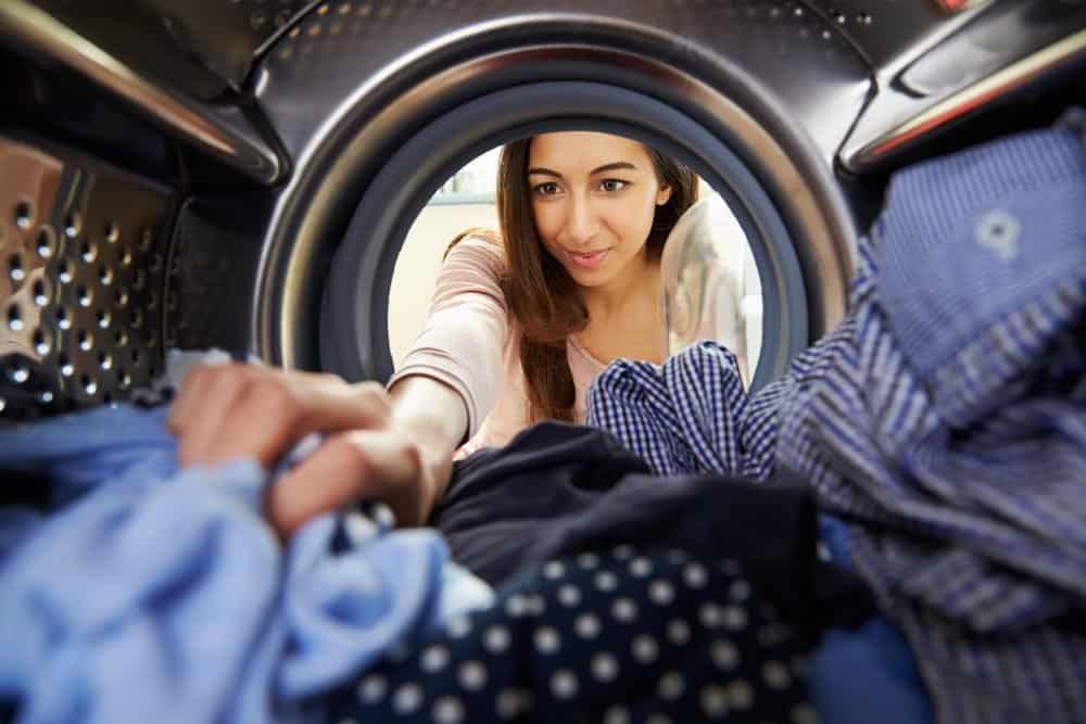 Woman doing laundry and reaching into a washing machine