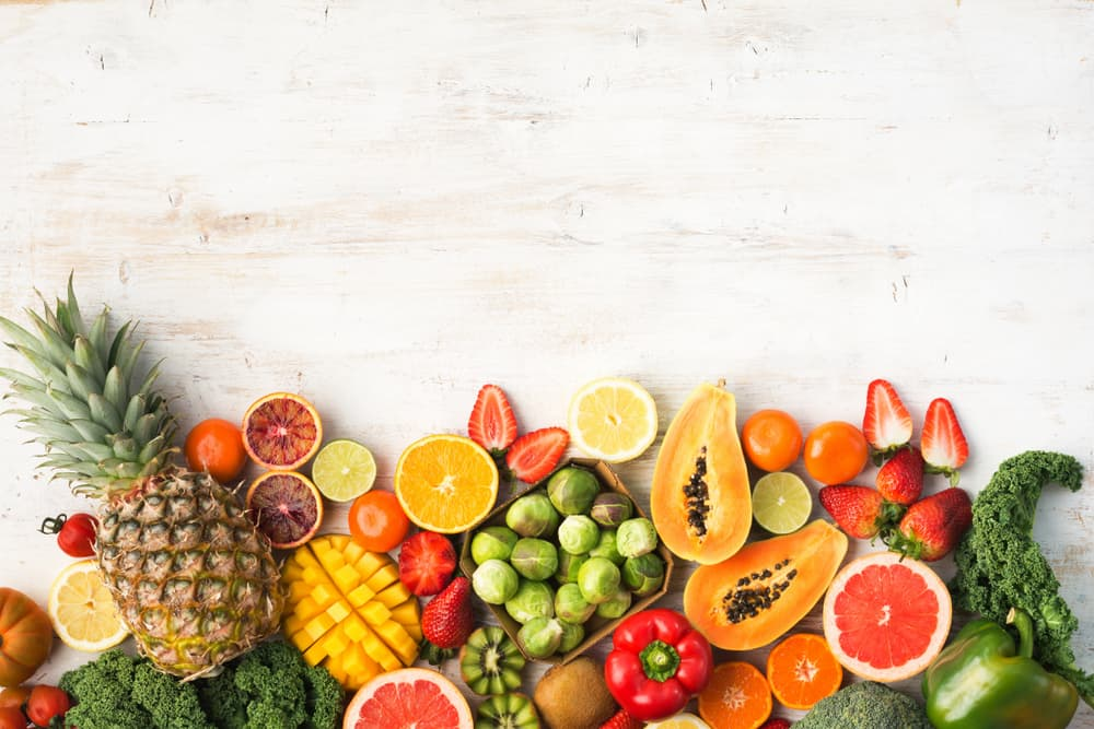 an array of fruits and vegetables sitting on a table