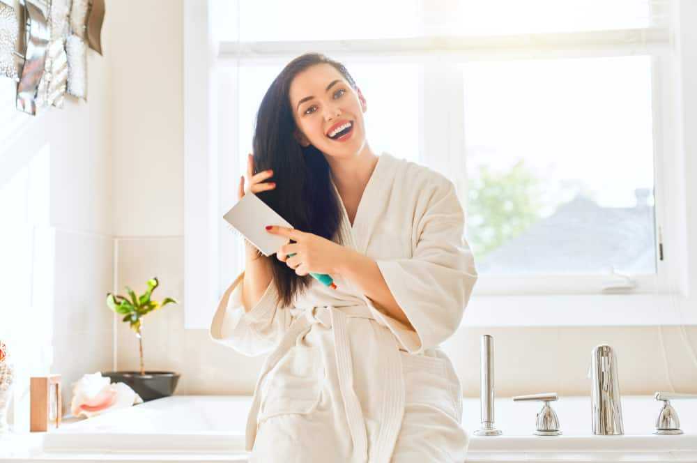 A woman smiles as she combs her hair in the bathroom