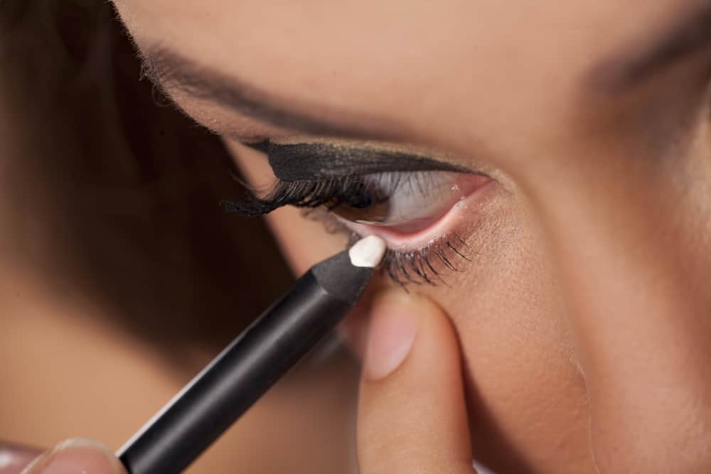 woman applying white eyeliner to the waterline