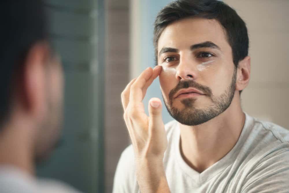man applying eye cream