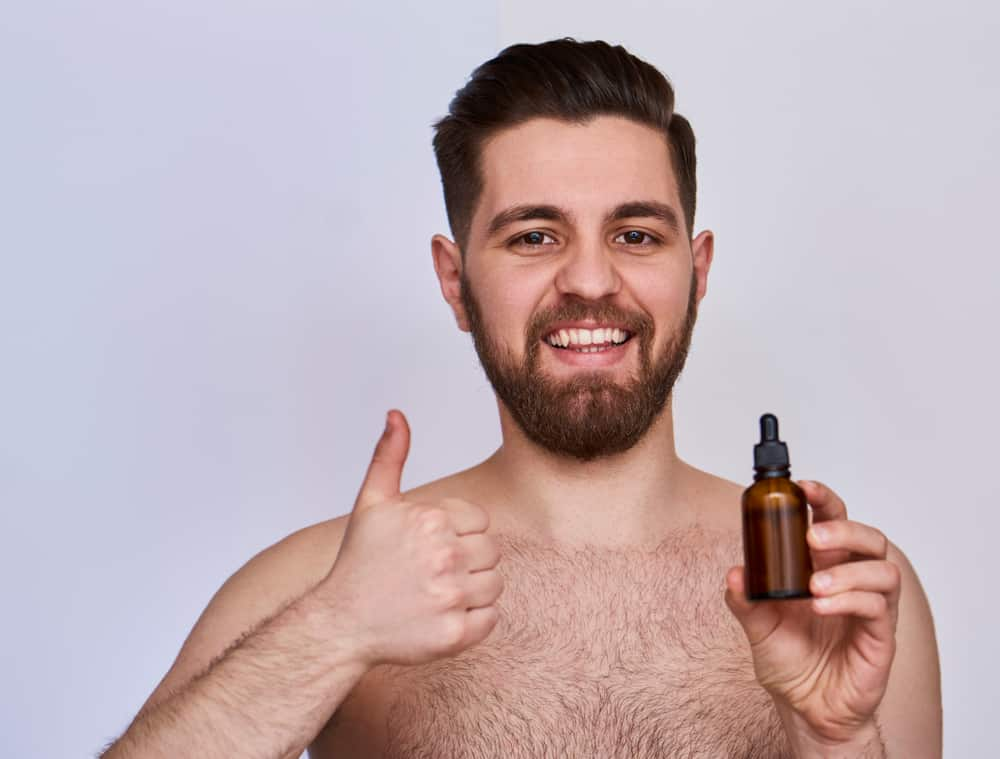 man holding a small bottle of beard oil