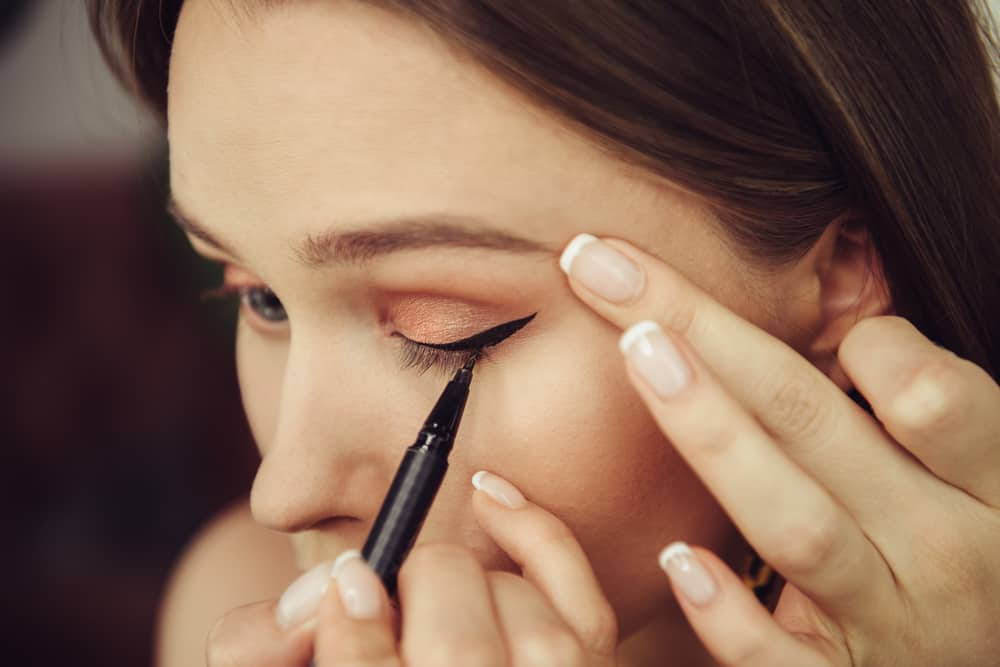 woman applying eyeliner on her eye