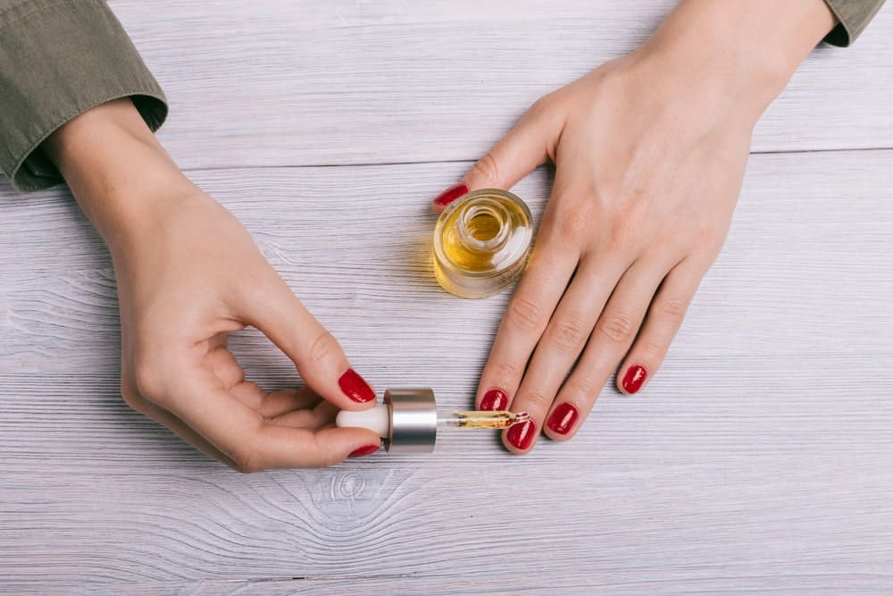 woman applying oil to nails