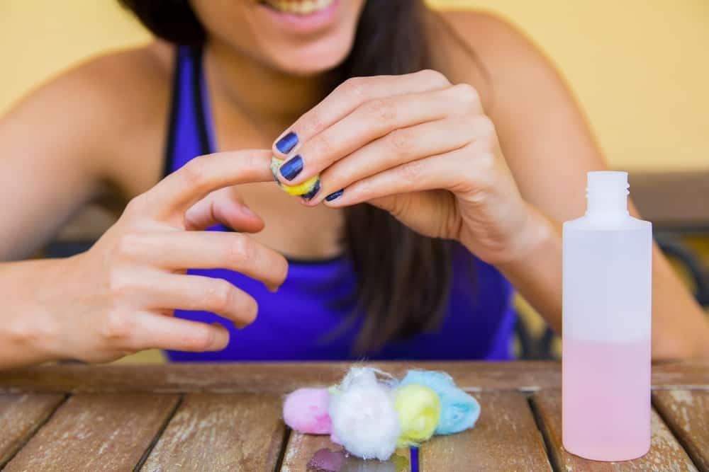 woman smiling while removing nail polish