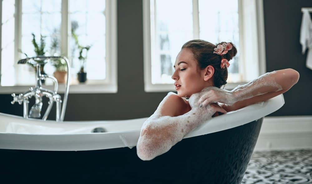 woman in bath with soap lathered on arms
