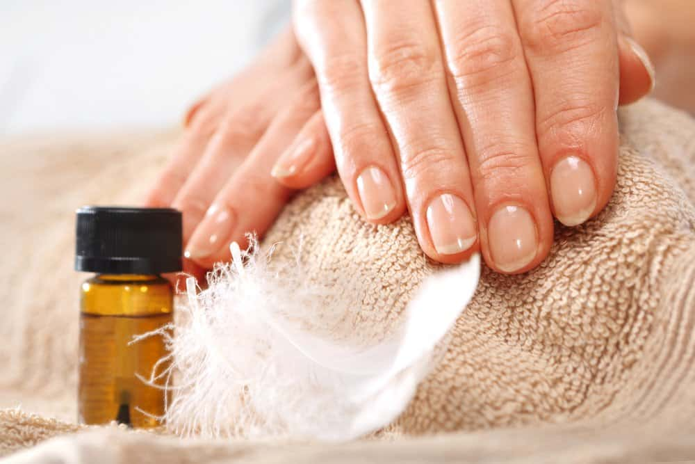 Manicured hands draped on a towel with a bottle of cuticle oil nearby