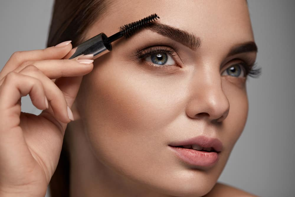 close up of model applying clear eyebrow gel