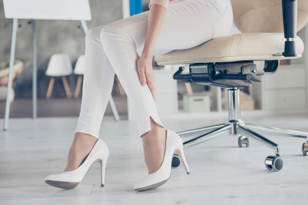 woman in office chair wearing white pumps