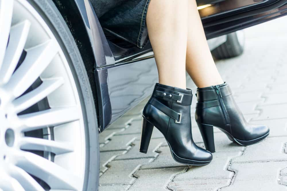 someone wearing black ankle booties stepping out of a car
