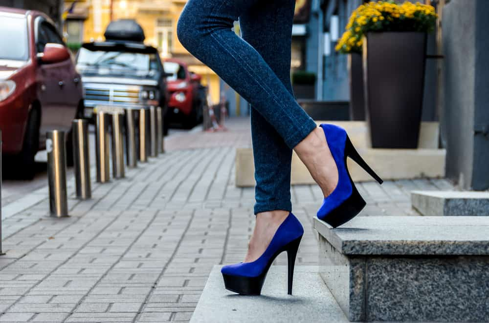 someone in jeans wearing blue and black platform stilettos