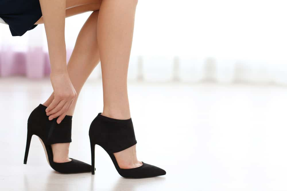 woman taking off black stiletto heels