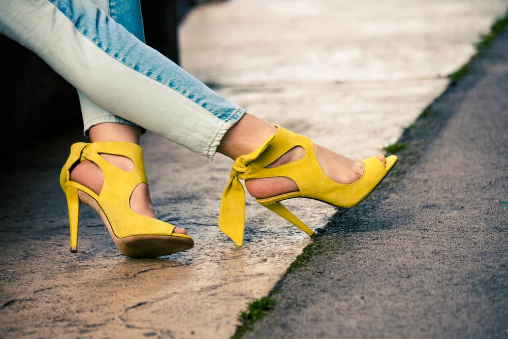 someone wearing jeans and yellow high heeled sandals
