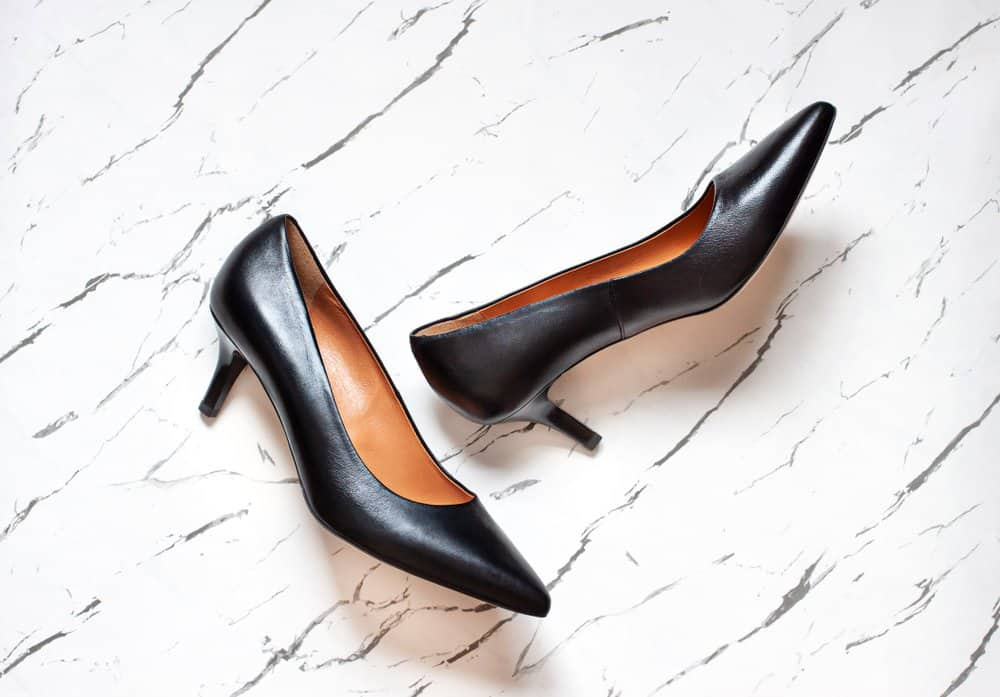 black kitten heel pumps on a white marble floor