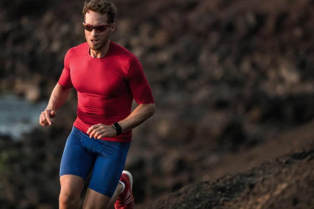 male athlete jogging through trail