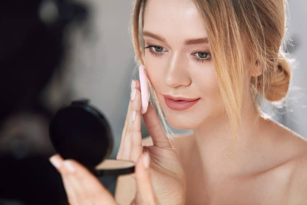 woman applying pressed powder