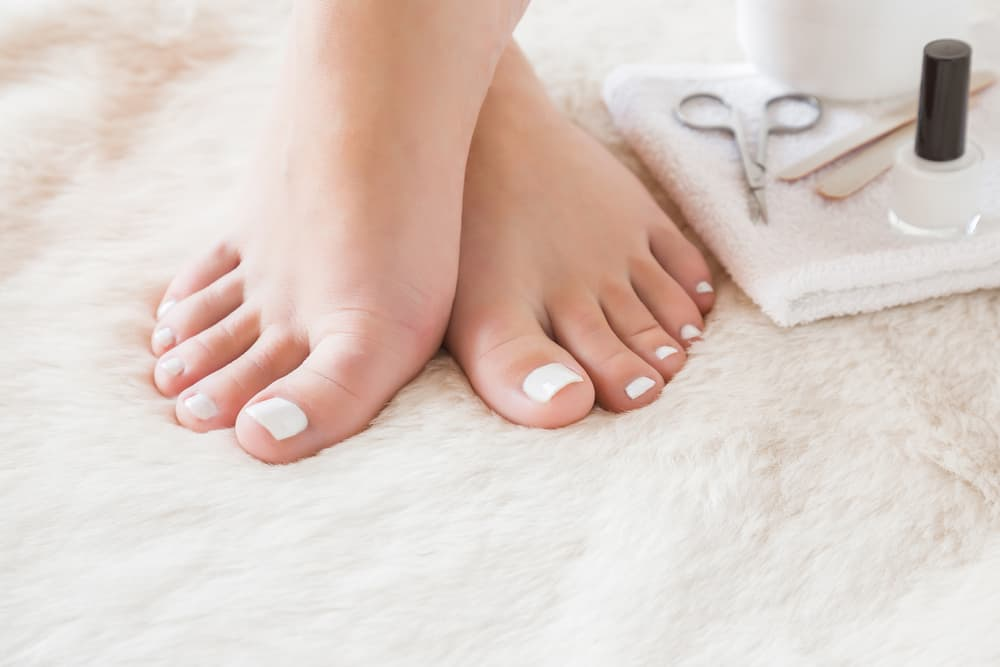 woman with painted white toenails
