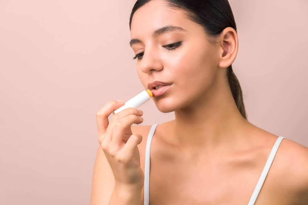 young woman applying yellow lip balm
