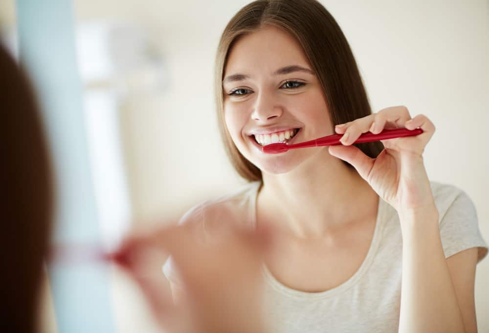 young woman brushing her teeth in front of mirror