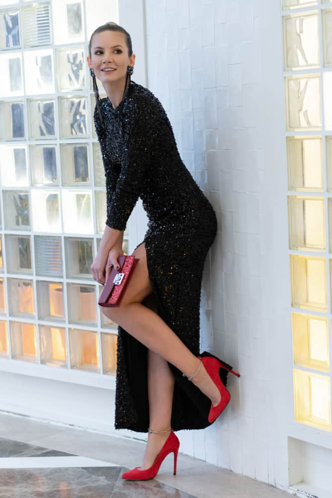 a young woman in a sequin, long-sleeve black dress and red heels