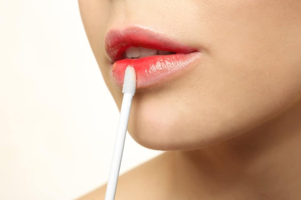 woman applying tinted lip gloss