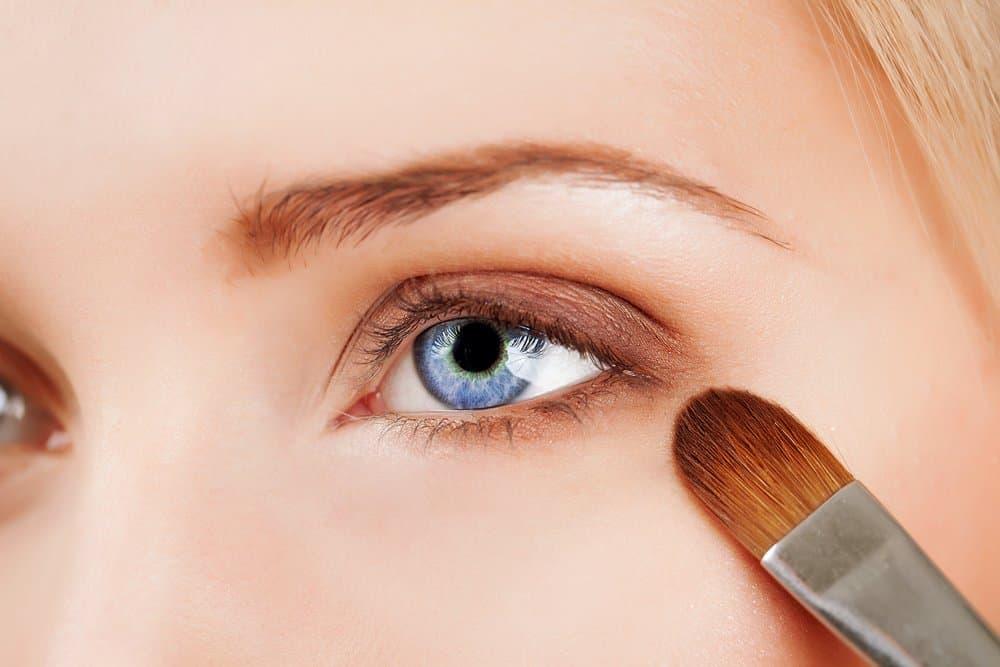 applying eyeshadow to blue eyes