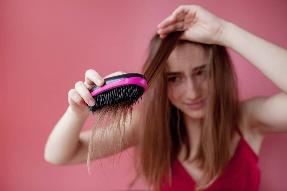 girl struggling to brush hair