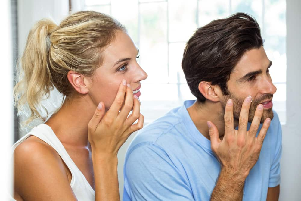 man and woman looking in mirror to apply moisturizer to face