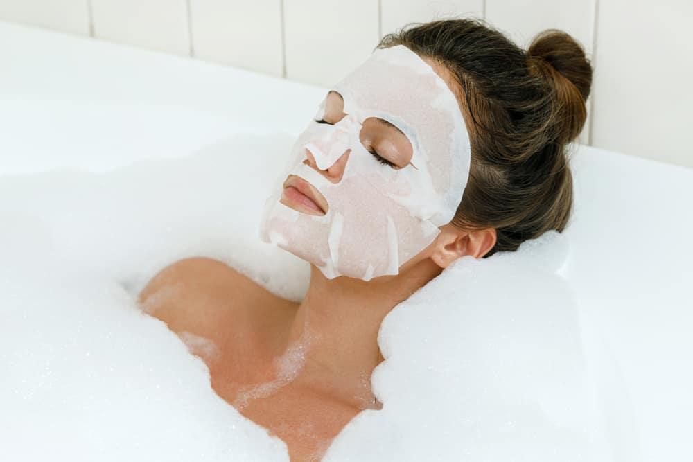 women wearing sheet mask in bubble bath