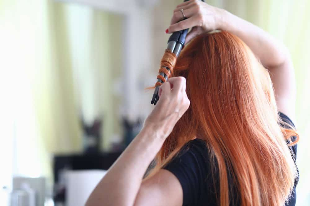 red-haired woman using curler