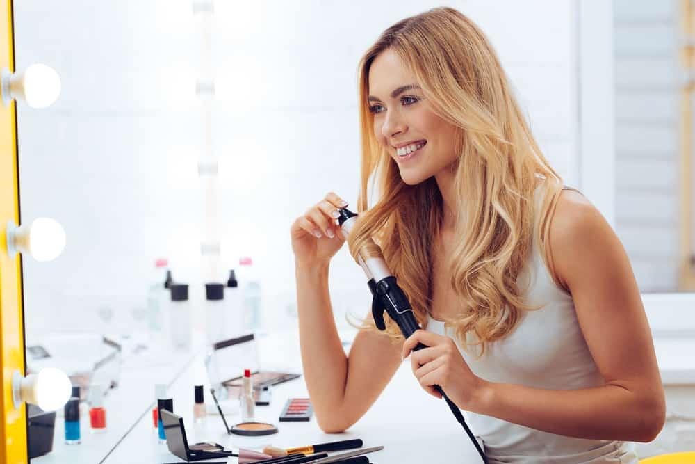woman curling hair in mirror