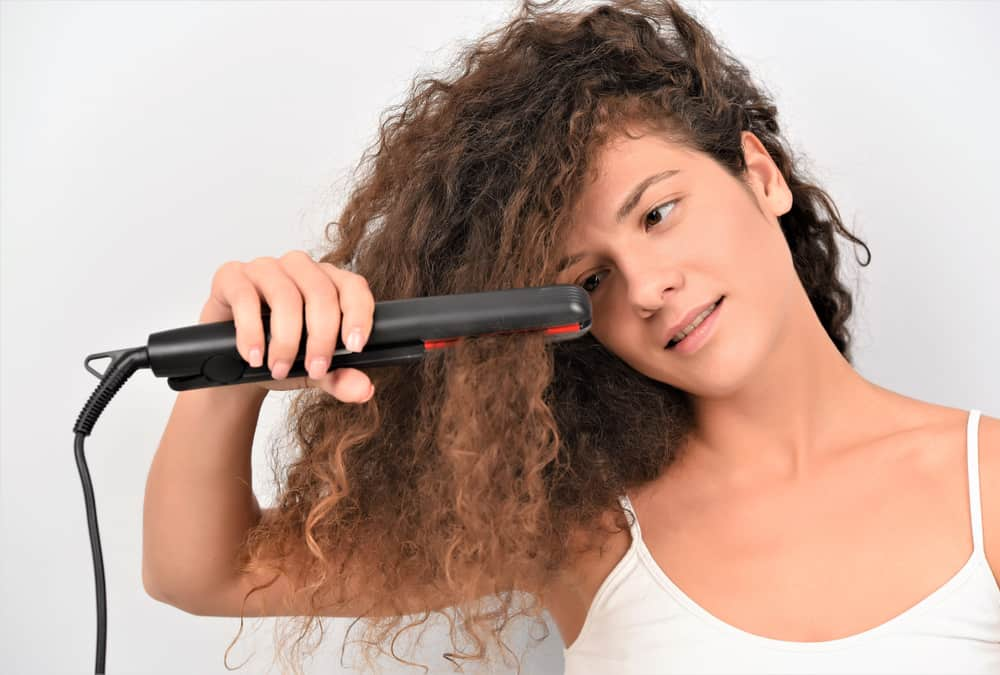 woman with curly hair and flat iron