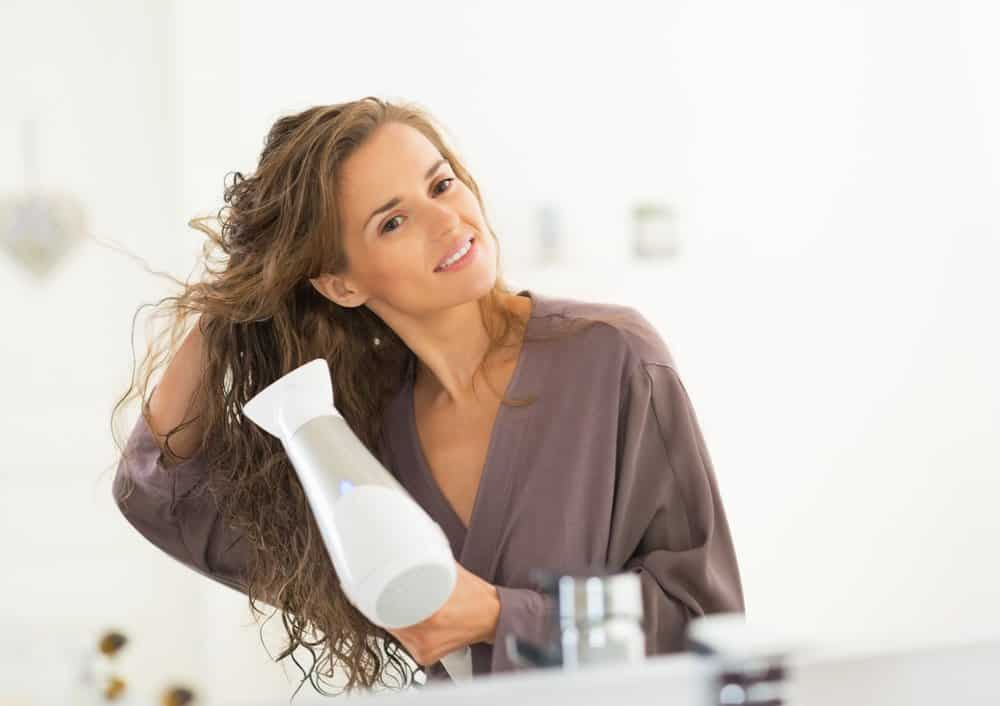 woman in gray silk bathrobe using hair dryer