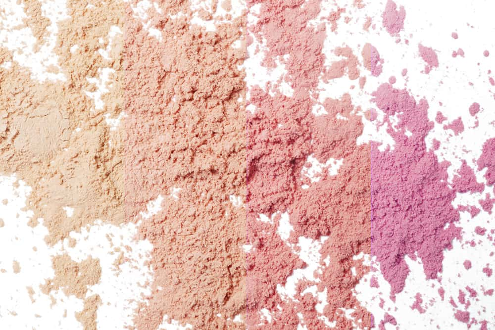 a bunch of cosmetic powders loosely piled on a white background