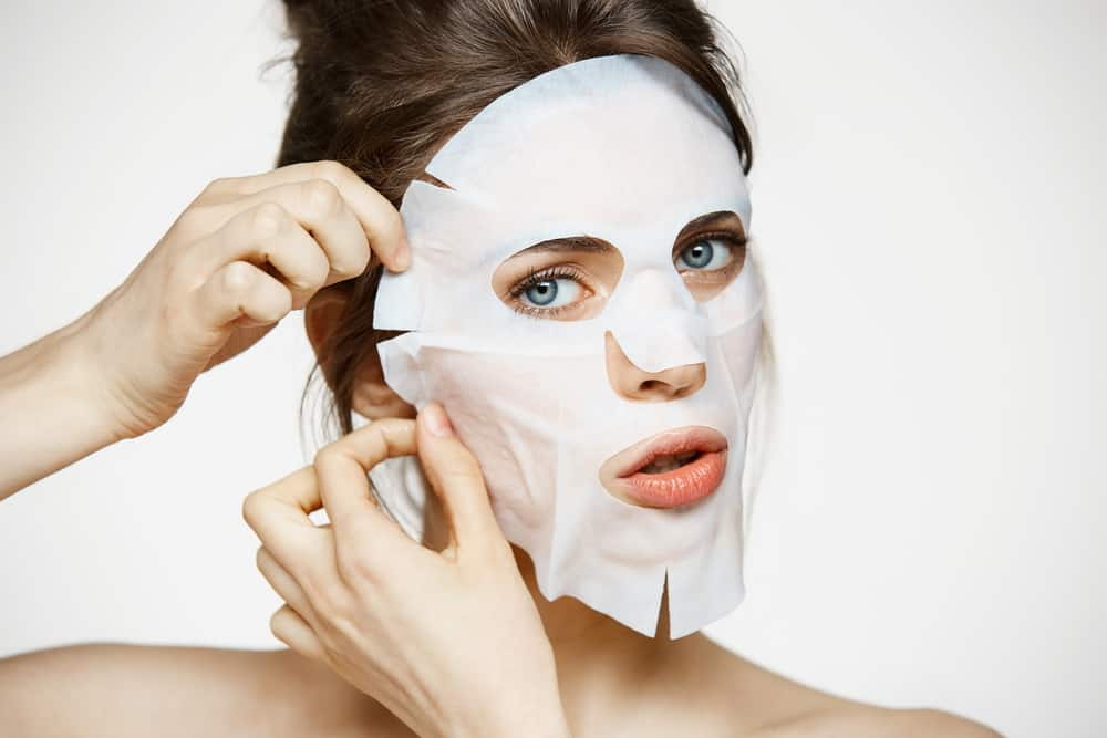 woman applying face mask on her face