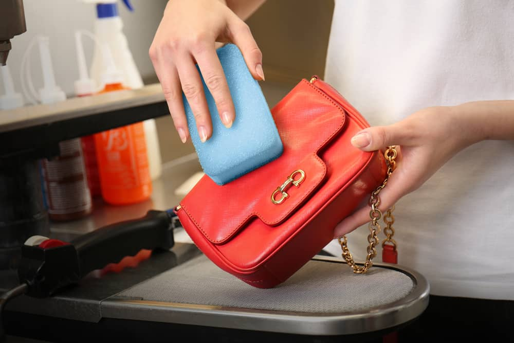 woman cleaning bag with sponge