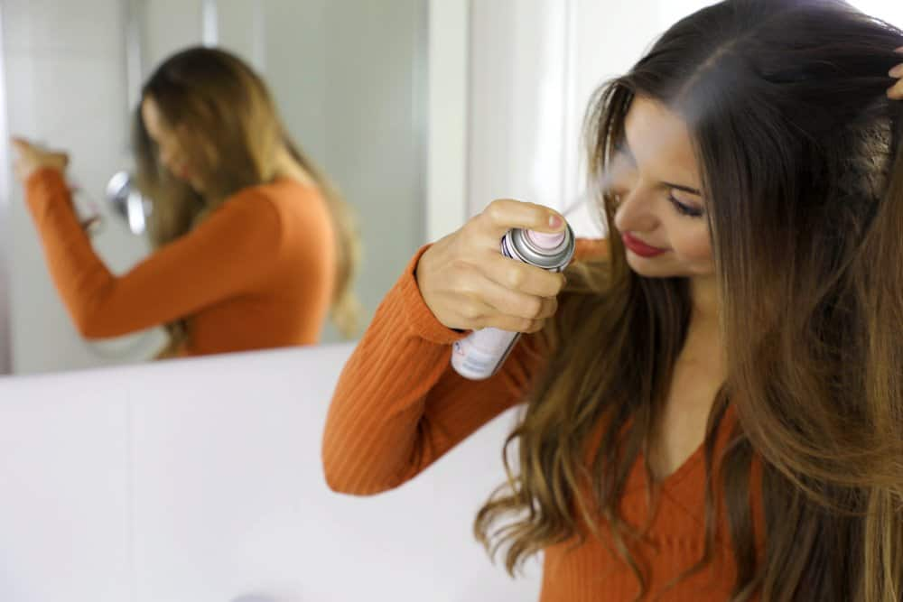 a woman applies a spray to the roots of her hair