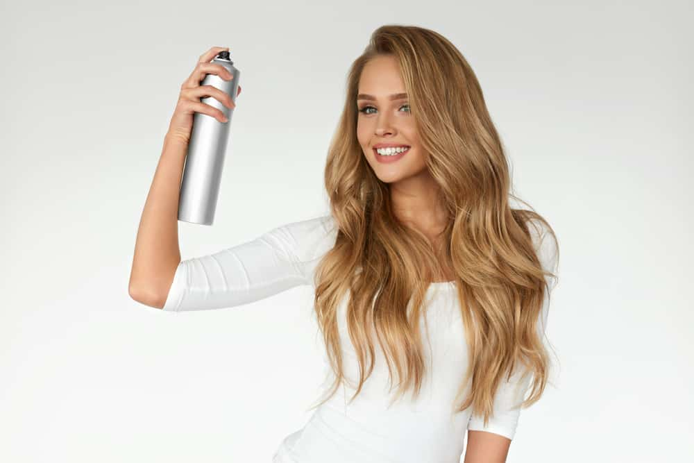 woman applying hairspray
