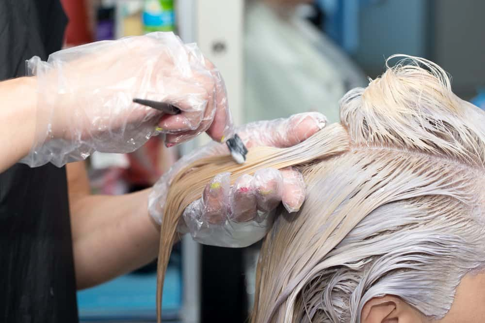 stylist bleaching customer's hair
