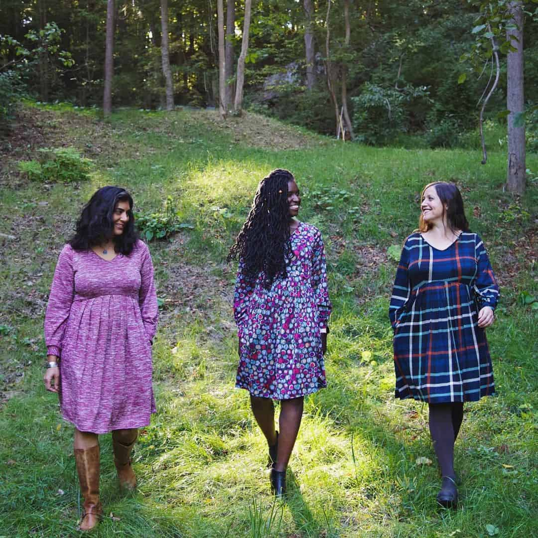 Three models in the forest in knee-length dresses