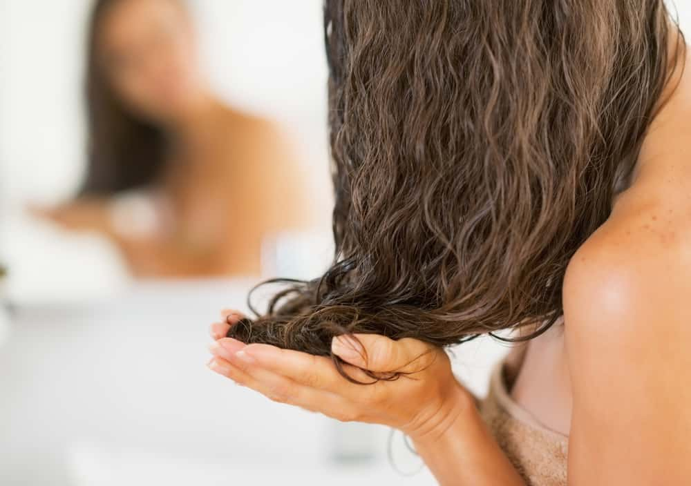 Woman applying moisturizer to hair
