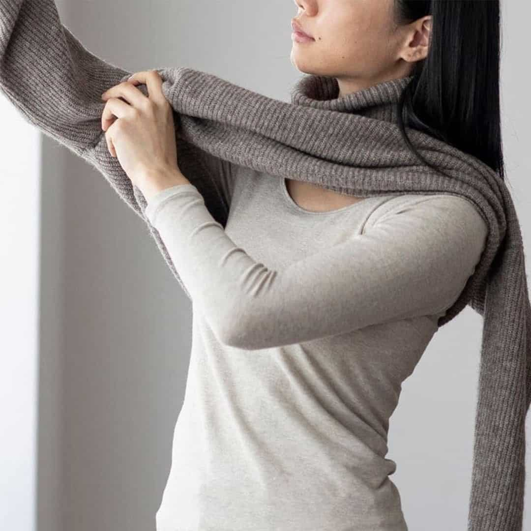 Woman pulling on a sweater