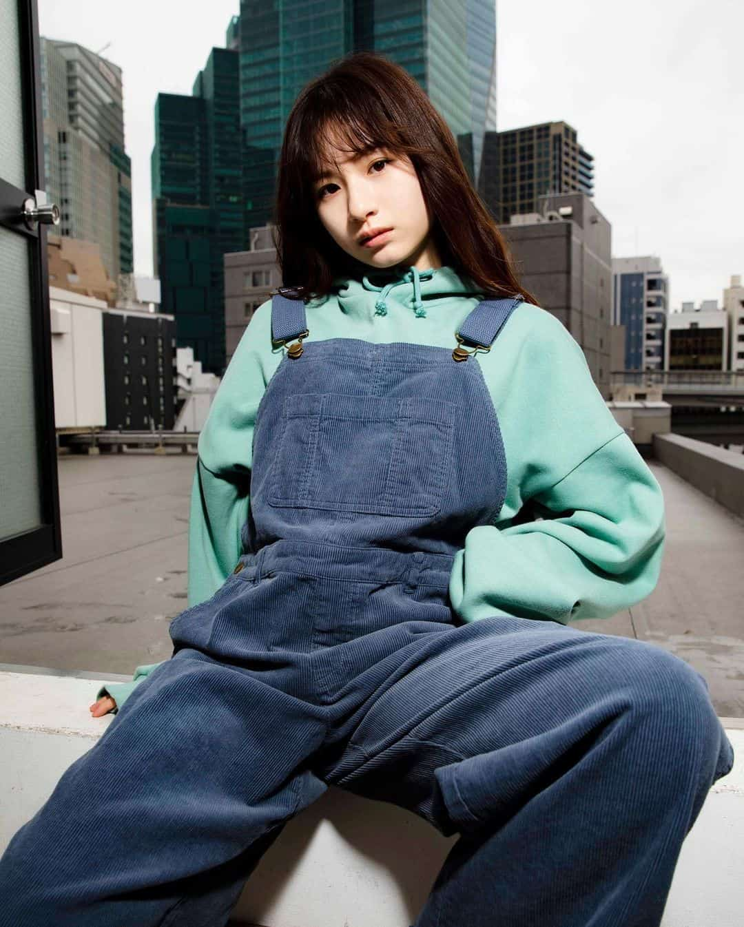 Young woman in pastel hoodie and denim overalls