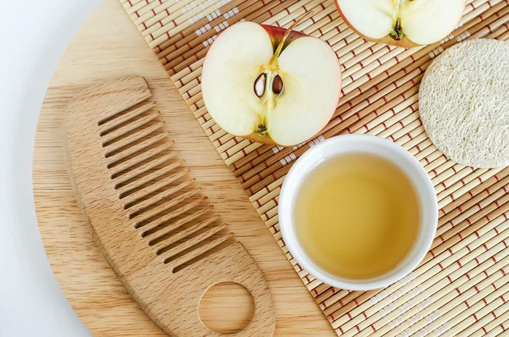apple half and vinegar and wooden comb