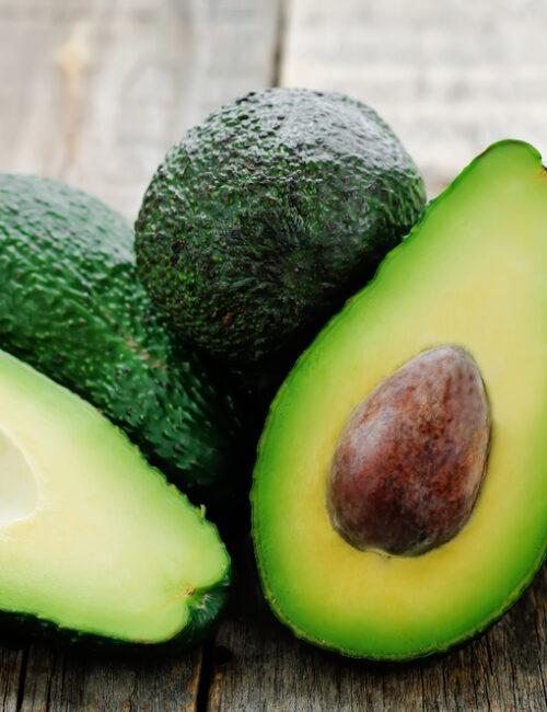 avocado halves resting on other avocados