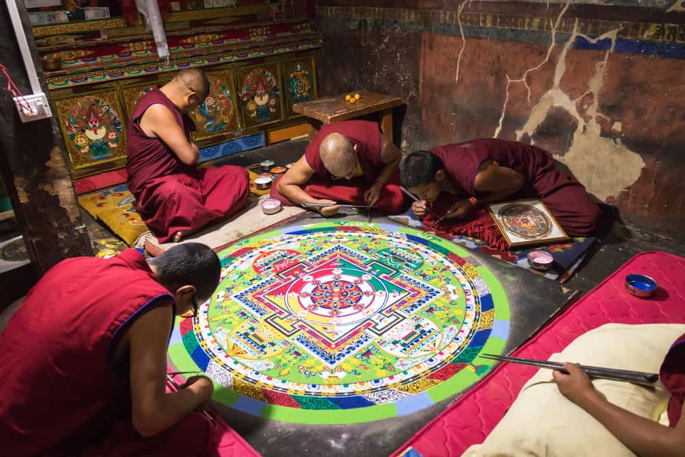 buddhist monks making sand mandala